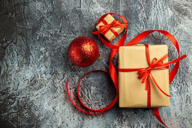 Bovenaanzicht klein cadeautje vastgebonden met rood lint rode kerstbal op donkere achtergrond