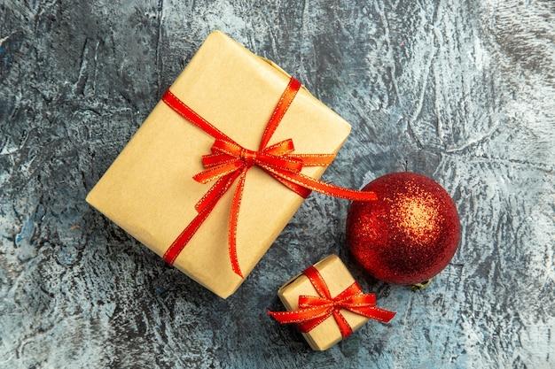 Bovenaanzicht klein cadeautje vastgebonden met rood lint rode kerstboom bal op donkere ondergrond