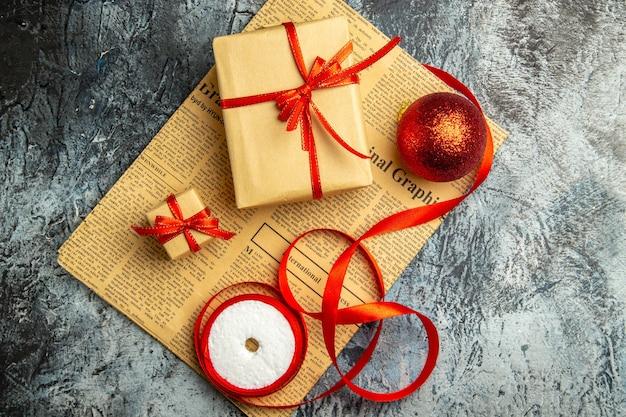 Bovenaanzicht klein cadeautje vastgebonden met rood lint rood ballint op krant op donkere ondergrond