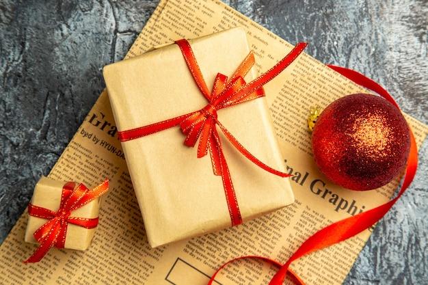 Bovenaanzicht klein cadeautje vastgebonden met rood lint rood kerstbal lint op krant op donkere ondergrond