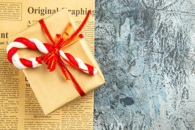Bovenaanzicht klein cadeautje vastgebonden met rood lint xmas snoep op krant op grijze ondergrond