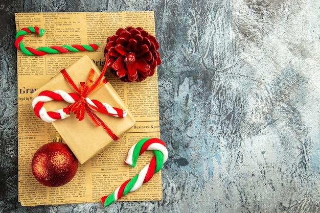Bovenaanzicht klein cadeautje vastgebonden met rood lint xmas snoepjes op krant op grijze ondergrond