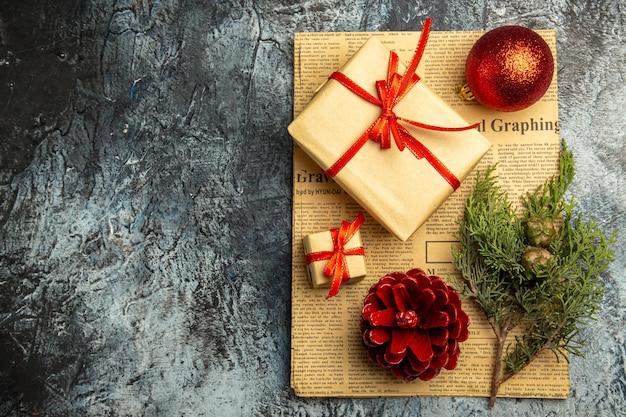 Bovenaanzicht klein geschenk gebonden met rood lint rode kerstbal dennentak op krant op donkere ondergrond