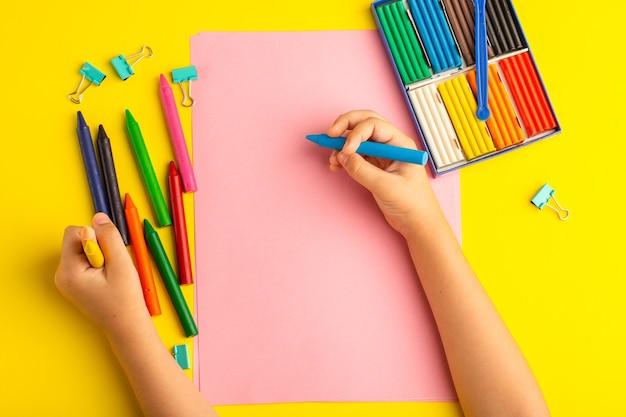 Bovenaanzicht klein kind met kleurrijke potloden op roze papier op geel oppervlak