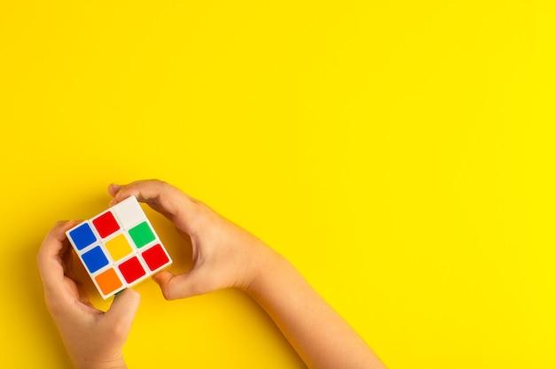 Bovenaanzicht klein kind spelen met rubics kubus op gele ondergrond