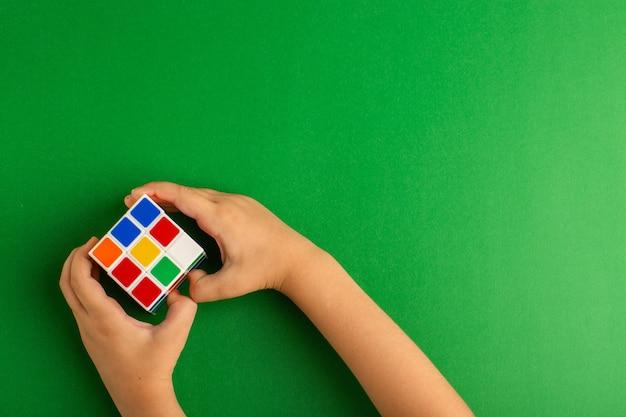 Bovenaanzicht klein kind spelen met rubics kubus op groene ondergrond
