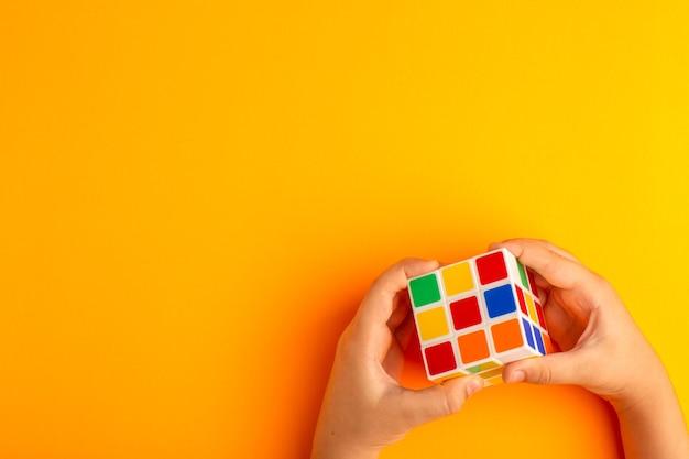Bovenaanzicht klein kind spelen met rubics kubus op het oranje bureau