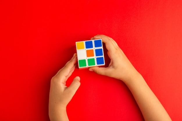 Bovenaanzicht klein kind spelen met rubics kubus op rood bureau