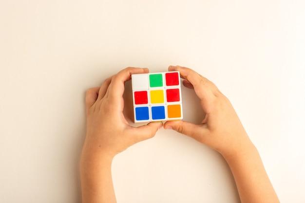 Bovenaanzicht klein kind spelen met rubics kubus op wit bureau