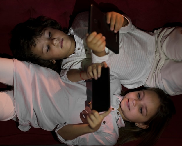 Bovenaanzicht kleine broers en zussen spelen op hun elektronische apparaten