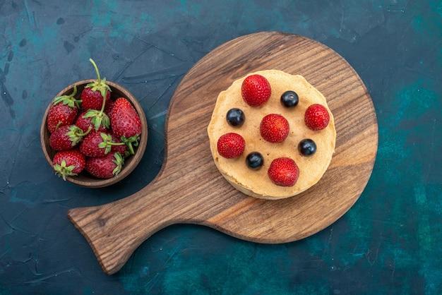 Bovenaanzicht kleine cake gebakken rond gevormd met verse aardbeien op het donkerblauwe oppervlak