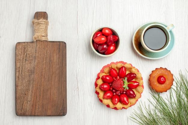 Bovenaanzicht kleine cake met fruit en kopje thee op wit bureau