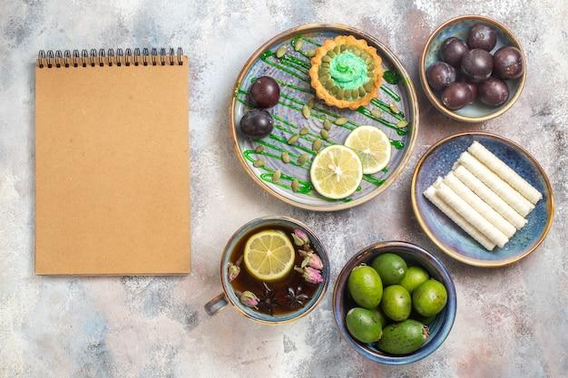 Bovenaanzicht kleine cake met fruit en thee