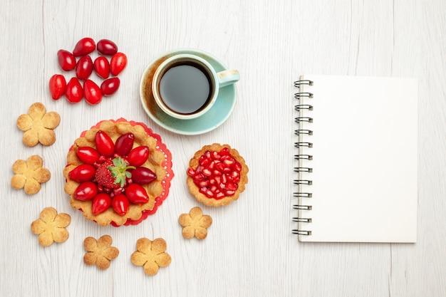 Bovenaanzicht kleine cake met fruit koekjes en kopje thee op wit bureau