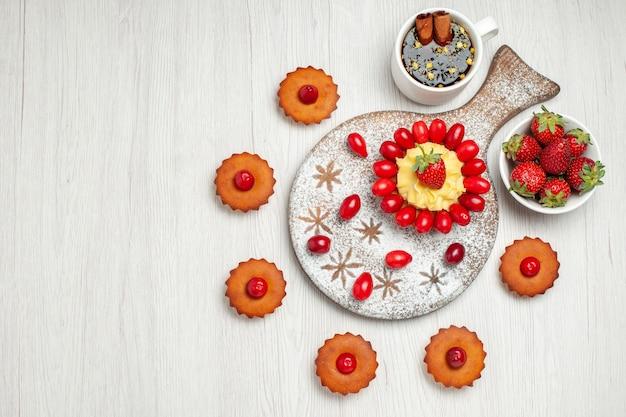 Bovenaanzicht kleine cake met fruit thee en gebak op wit bureau