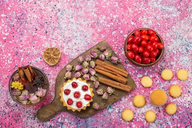 Bovenaanzicht kleine cake met room samen met kaneelkoekjes thee en rood fruit op het paarse oppervlak zoet fruit