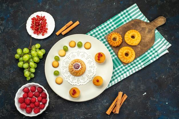 Bovenaanzicht kleine cake met roomkoekjes en groene druiven, frambozen en veenbessen op het donkere bureau