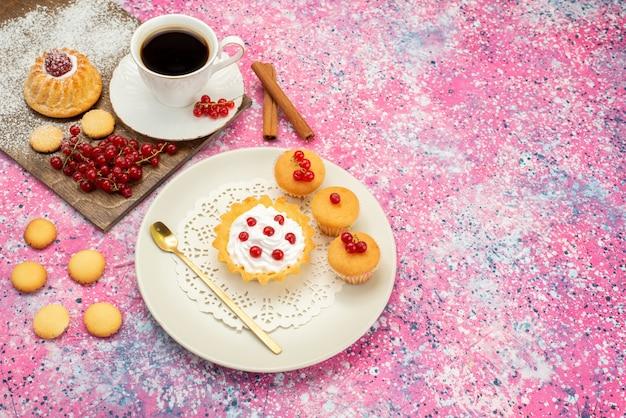 Bovenaanzicht kleine cake met roomkoekjes verse veenbessen samen met een kopje koffie en kaneel op de gekleurde oppervlakkoekjes