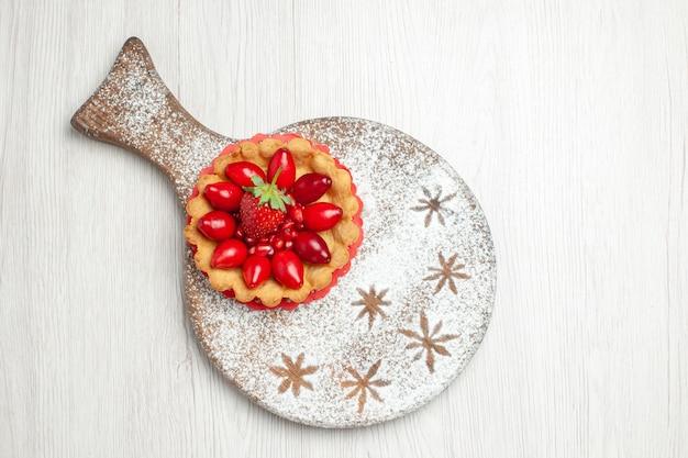 Bovenaanzicht kleine cake met vers fruit op wit bureau
