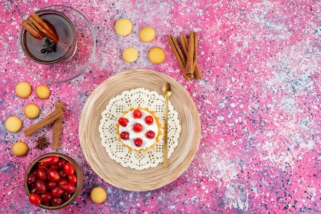 Bovenaanzicht kleine cake met verse room en vers fruit, samen met kaneel en kopje thee op het heldere bureau cake zoet