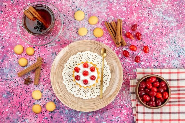 Bovenaanzicht kleine cake met verse room en vers fruit samen met kaneel en thee op het heldere bureaukoekje
