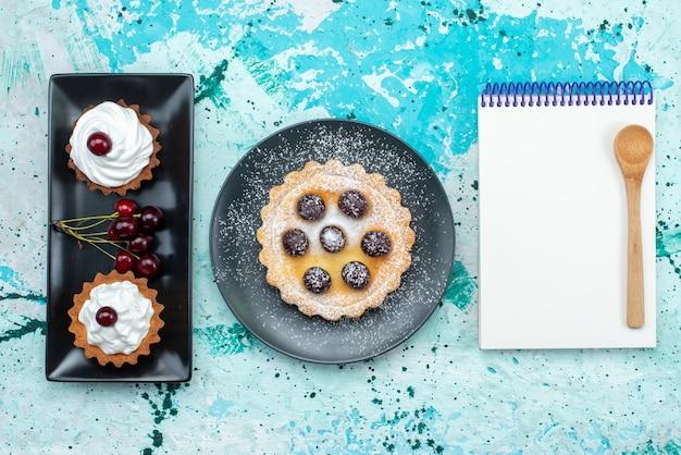 Bovenaanzicht kleine cakejes met room en fruit samen met blocnote op de lichtblauwe tafel fruit bakken slagroomtaart