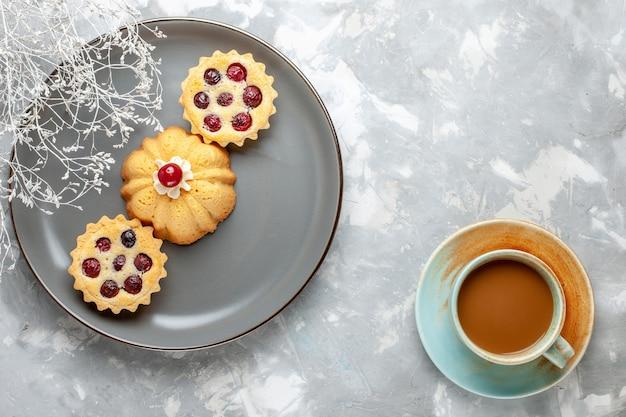 Bovenaanzicht kleine cakes in grijze plaat met melkkoffie op het licht bureau cake biscuit koffie suiker zoet