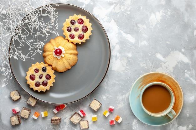 Bovenaanzicht kleine cakes in grijze plaat met melkkoffie op licht bureau koekje koffiesuiker zoet