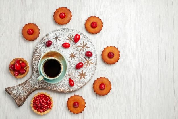 Bovenaanzicht kleine cakes met fruit en kopje thee op licht wit bureau