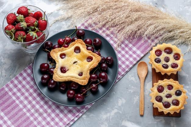 Bovenaanzicht kleine cakes met fruit en room samen met verse kersen aardbeien op licht bureau cake room fruit zoete thee