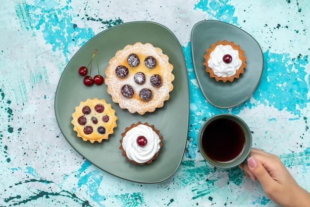 Bovenaanzicht kleine cakes met fruit in de plaat samen met thee op de helderblauwe tafel