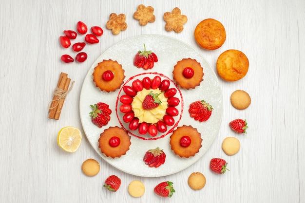 Bovenaanzicht kleine cakes met fruit in plaat op wit bureau