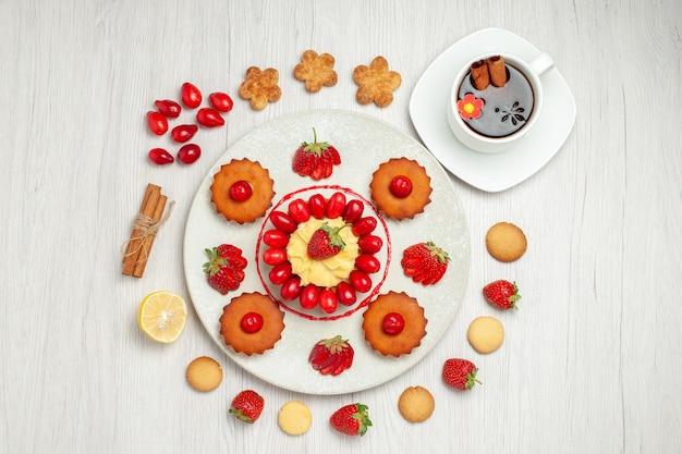 Bovenaanzicht kleine cakes met fruit in plaat op witte vloer