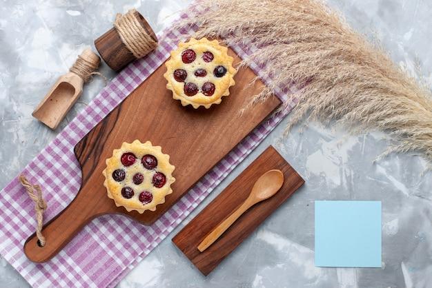Bovenaanzicht kleine cakes met fruit op lichtgrijze tafel thee zoete cake bakken taart