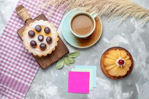 Bovenaanzicht kleine cakes met fruit samen met koffie op de licht bureau cake koekje zoet bakken
