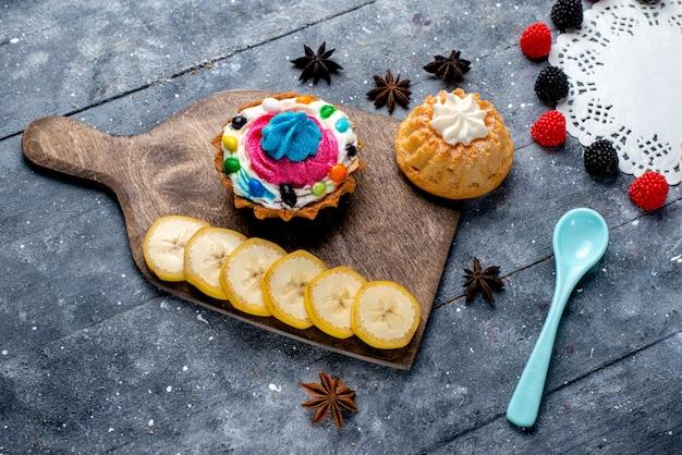 Bovenaanzicht kleine cakes met room samen met gesneden fruit bessen blauwe lepel op de lichte tafel cake koekje zoete suiker fruit