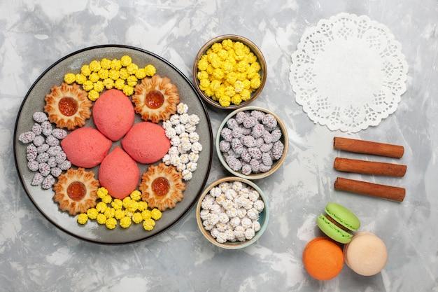 Bovenaanzicht kleine cakes met snoepjes en koekjes op witte ondergrond koekjes suiker zoet koekje koekje