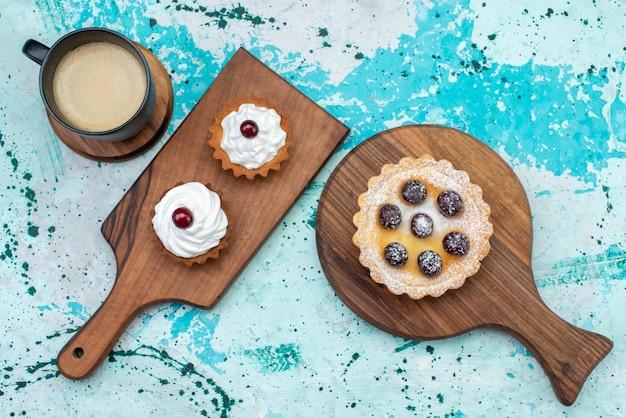 Bovenaanzicht kleine cakes met suikerpoeder fruitroom en op lichtblauwe vloer cake crème fruit zoete thee