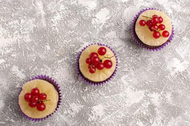 Bovenaanzicht kleine chocoladetaartjes met veenbessen erop en op de lichte achtergrond fruit bessen cake zoet bakken