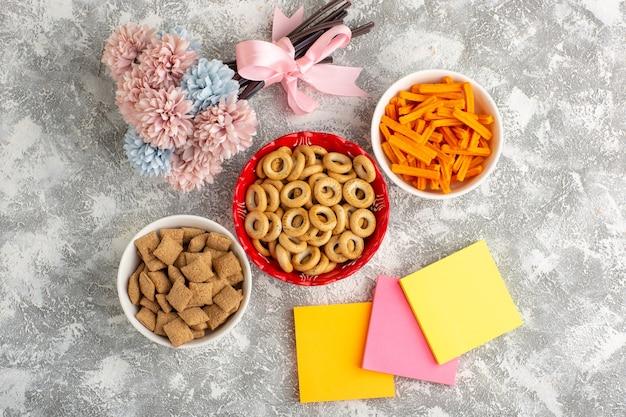 Bovenaanzicht kleine crackers met kussenkoekjes en beschuit op witte ondergrond