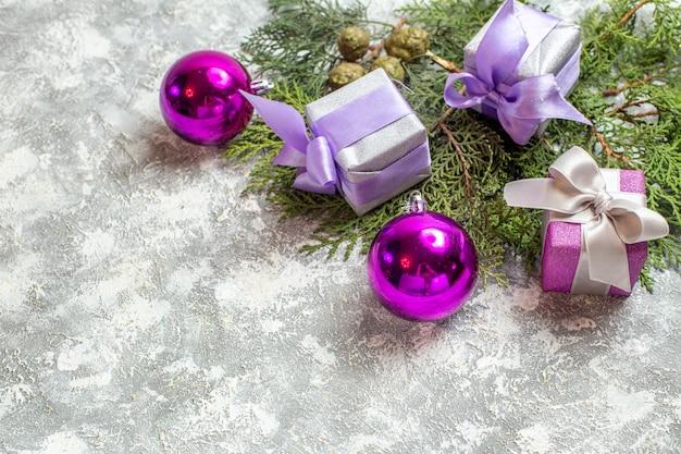 Bovenaanzicht kleine geschenken dennenboom takken kerstboom speelgoed op grijs oppervlak