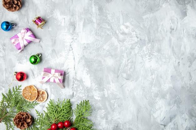 Bovenaanzicht kleine geschenken dennenboom takken kerstboom speelgoed op grijze achtergrond kopie ruimte