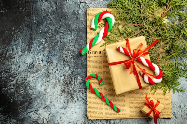 Bovenaanzicht kleine geschenken vastgebonden met rood lint kerstsnoepjes op krantenpijnboomtakken op grijs oppervlak
