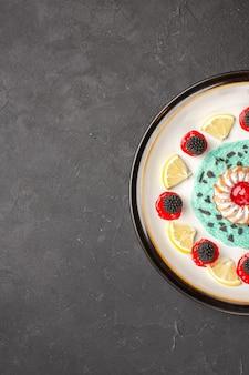 Bovenaanzicht kleine heerlijke cake met confitures en schijfjes citroen in plaat op donkere achtergrond, fruit, citruskoekje, zoet?