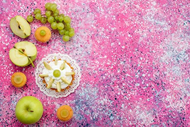 Bovenaanzicht kleine heerlijke cake met gesneden fruit en room op de gekleurde achtergrond cake zoete suikerkleur