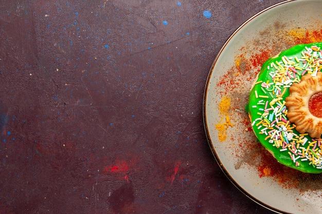 Bovenaanzicht kleine heerlijke cake met groene room op het donkere oppervlak