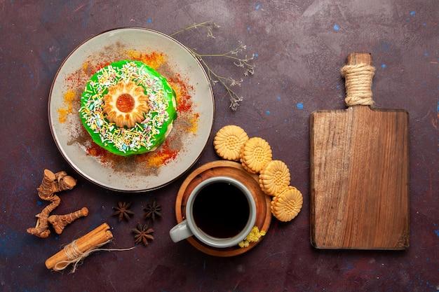 Bovenaanzicht kleine heerlijke cake met koekjes en kopje thee op het donkere oppervlak