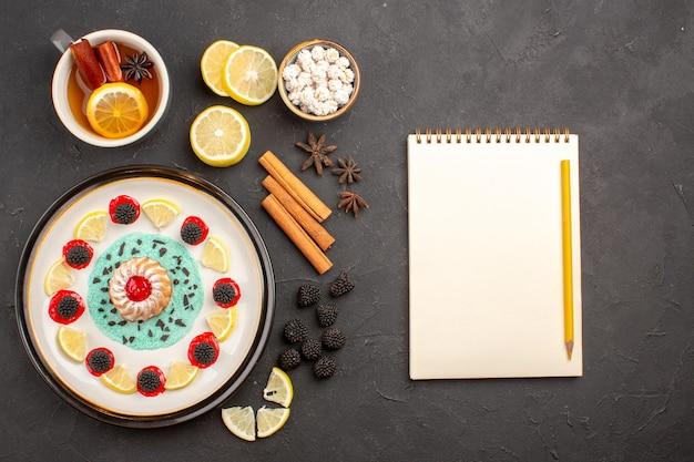 Bovenaanzicht kleine heerlijke cake met schijfjes citroen en kopje thee op de donkere achtergrond, fruit, citruskoekjeskoekje, zoet