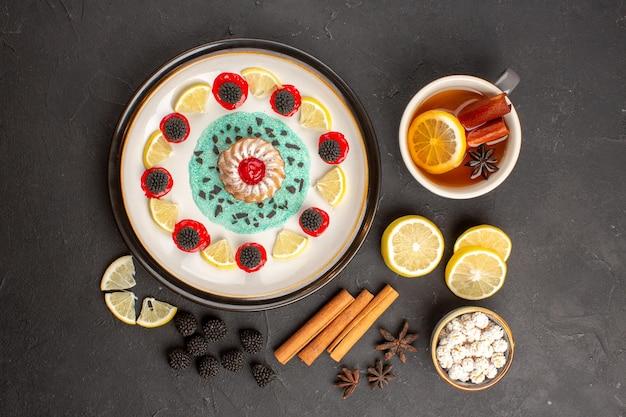 Bovenaanzicht kleine heerlijke cake met schijfjes citroen en kopje thee op een donkere achtergrond, fruit, citruskoekje, zoet?