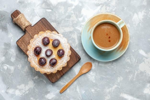 Bovenaanzicht kleine heerlijke cake met suikerpoeder en melkkoffie op het lichte bureau zoete koekje bak suikerfoto
